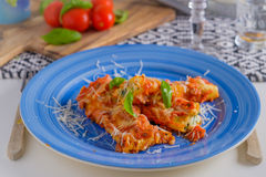 Cannelloni pasta dish with tomatoe sauce on a blue plate with to Royalty Free Stock Image