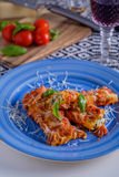 Cannelloni pasta dish with tomatoe sauce on a blue plate with to Stock Photo
