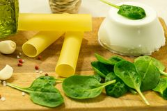 Cannelloni with ricotta and spinach on wooden table. Traditional Italian food ingredients.Italian cuisine stock image