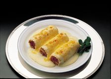 Cannelloni stuffed with meat with bechamel sauce. On round plate and on black background Royalty Free Stock Images