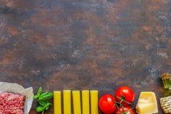 Cannelloni, Tomaten, Hackfleisch und andere Bestandteile Dunkler Hintergrund Italienische K?che stockbilder