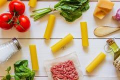 Cannelloni, Tomaten, Hackfleisch und andere Bestandteile Wei?er h?lzerner Hintergrund Italienische K?che stockbilder