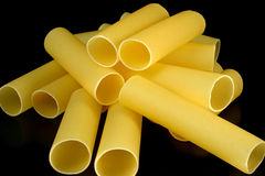 Cannelloni tubes - random heap. Cannelloni pasta tubes on a black background Stock Image