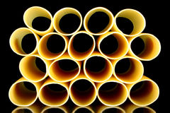 Cannelloni tubes - stacked view. Cannelloni pasta tubes on a black background Stock Image