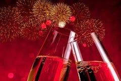 Cannelures de Champagne avec les bulles d'or sur le bokeh de lumière rouge et le fond d'étincelle de feux d'artifice Photographie stock libre de droits