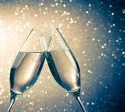 Cannelures de Champagne avec les bulles d'or sur le fond clair bleu de bokeh Photos stock