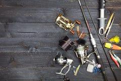 Cannes à pêche et bobines, articles de pêche sur le backgroun en bois noir Photo libre de droits