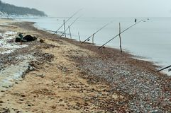 Cannes à pêche sur le bord de mer, pêche d'hiver en mer, cannes à pêche placées sur le rivage de l'étang Image stock