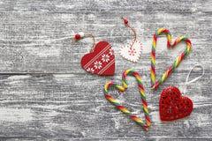 Cannes de sucrerie de Noël et coeurs de décorations sur le tabl en bois gris Images libres de droits