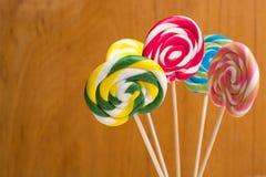 Cannes de sucrerie douces multicolores et pirouettes sur les bâtons en bois Images stock