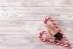 Cannes de sucrerie et cadeau de Noël sur le fond en bois brun Images stock
