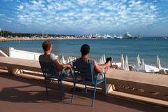 CANNES, FRANCE - 5 JUILLET 2014 : Deux amis détendant dans les chaises o Image libre de droits