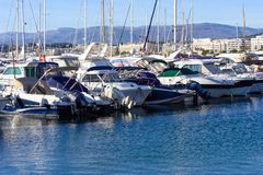 Cannes, France, March 2019. White expensive yachts on a background of mountains on a sunny day. Yacht parking in Cannes, France. Mediterranean Sea royalty free stock photo