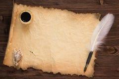 Cannette avec l'encrier sur le fond de papier de vintage et la table en bois Photographie stock