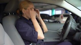 Cannette de fil femelle sûre mettant sur des lunettes de soleil se reposant sur le siège conducteur dans la voiture de patrouille clips vidéos