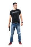 Cannette de fil simple macho sûre de vêtements avec l'arme à feu regardant loin avec précaution Images stock