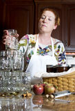 Canning. Woman canning home made apple butter in her kitchen royalty free stock photo