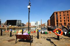 Canning Dock, Liverpool. Two ladies sitting on a bench looking across Canning Dock with The Pumphouse and city to the rear, Liverpool, Merseyside, England, UK Royalty Free Stock Image