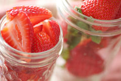 Canning jars with strawberries. Cut up berries in glass canning jars stock photo