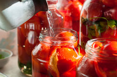 Canning process of tomato in mason jar. On. Background is few jars with tomatoes. Conservation and cooking stock image