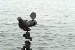Cannocchiale di portata di macchia di birdwatching su un treppiede vicino all'acqua fotografie stock libere da diritti