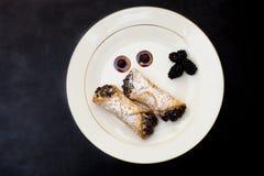 Cannoli italiano com os pedaços de chocolate na placa branca sobre o fundo preto fotos de stock royalty free