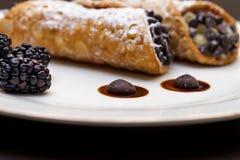 Cannoli italiano com os pedaços de chocolate na placa branca sobre o fundo preto imagens de stock royalty free