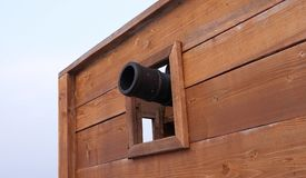 Cannon aiming out of wooden opening. An old cannon aiming out of a wooden opening on a ship Royalty Free Stock Image