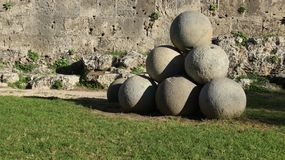 Cannon Ball And Stone Walls. Cannon ball. stone ball and green grass with warm sunlight and old stone walls in historic town Rhodes Greece stock photo