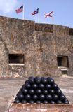 Cannon balls at Puerto Rican Fort. A stack of cannon balls in a Puerto Rican fort, showing flags of the USA and Puerto Rico Royalty Free Stock Image