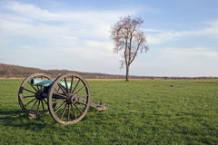 Cannon on battlefield. A muzzle loaded brass cannon, green with age, sits mutely on a Civil War battlefield in Missouri, with a lone tree in the background in Stock Photo