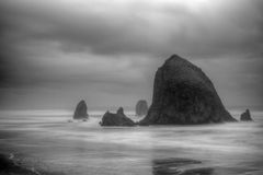 Cannon Beach. Iconic Haystack Rock on shore of Cannon Beach in Oregon with waves washing around it to the shore and with dramatic cloudy sky all in black and Royalty Free Stock Photo