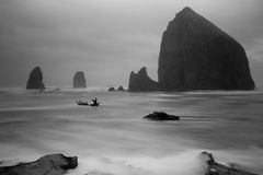Cannon Beach. Iconic Haystack rock on shore of Cannon Beach in Oregon with waves washing around it to the shore and with dramatic cloudy sky all in black and Royalty Free Stock Photos