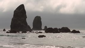 Cannon Beach Haystack Rock Pinnacles 4K. UHD. Fog behind pinnacles at Cannon Beach, Oregon as the surf washes up onto the beach. United States. 4K, UHD stock video