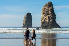 A couple walks enjoying the sun at Cannon beach, Oregon, USA. royalty free stock image