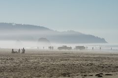 Tourists and locals enjoying the sun at Cannon beach, Oregon, USA. stock images