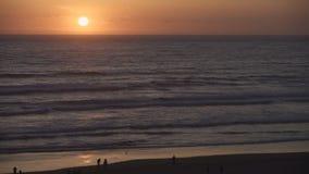 Cannon Beach Sunset, Oregon Coast 4K. UHD. People enjoying the sunset in Cannon Beach, Oregon as the surf washes up onto the beach. United States. 4K, UHD stock video footage