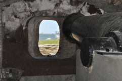 Cannon by an Embrasure at Fort Sumter. View from behind a cannon, looking out an embrasure window at Fort Sumter in Charleston, South Carolina royalty free stock photo