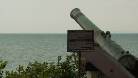 Cannon Gun Pointing To The Sea, Fort Cornwallis. Close-up low-angle still shot of a colonial cannon gun pointing towards the cloudy calm sea. Next to it is a stock video footage