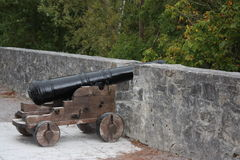 Cannon next to a wall. On a wooden wheeled strcture royalty free stock photography