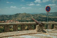Cannon overlooking hilly landscape in Monsanto. Old iron cannon over stone parapet and NO PARKING road sign, overlooking hilly landscape in a sunny day at stock image