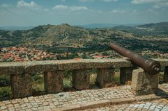 Cannon overlooking hilly landscape in Monsanto. Old iron cannon over stone parapet overlooking hilly landscape with houses rooftops, in a sunny day at Monsanto royalty free stock image