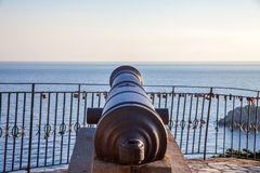 A cannon pointing towards the sea. The ancient artillery sitting above the concrete block. A calm sea surrounds the statue. Revolu stock photography