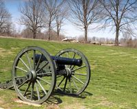 Cannon sitting on grass with trees and rocks in background. Cannon on the site of Wilson Creek National Battlefield, where the first major Civil War battle west Royalty Free Stock Image