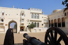 Cannon standing guard. Old city with various buildings Royalty Free Stock Photography
