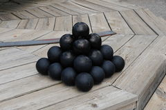 Cannonballs sitting on top a Cannonball gun turret ready for loading. Stock Photos