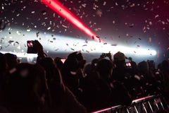Cannoni dei coriandoli che gettano i coriandoli sopra la folla facente festa Immagini Stock