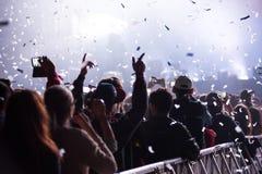 Cannoni dei coriandoli che gettano i coriandoli sopra la folla facente festa Immagine Stock