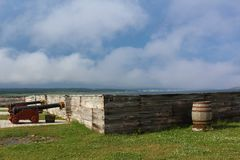 Cannons and a barrel by a wooden wall at the fortress of Louisburg with the town of Louisburg in the distance on a misty day Stock Images