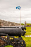 Cannons at fort george, scottish flag in the background Stock Image